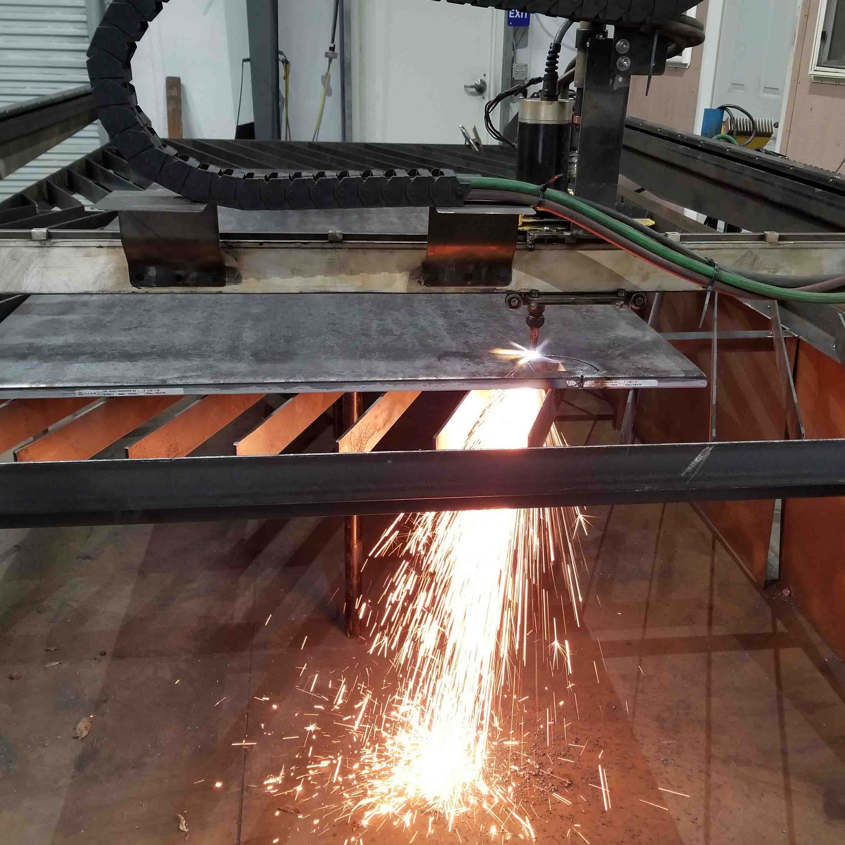 Picture of a CNC plasma table, with torch running.